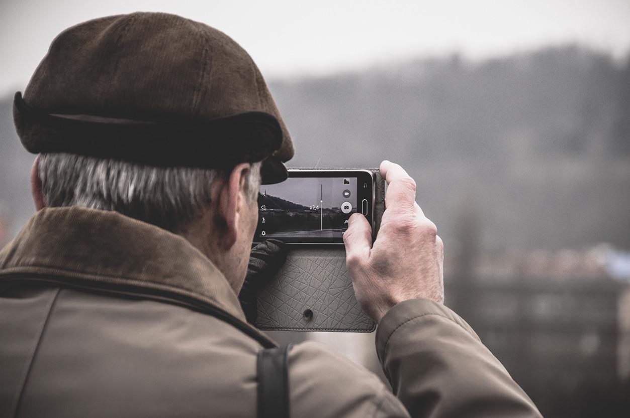 Senhor fotografando com smartphone