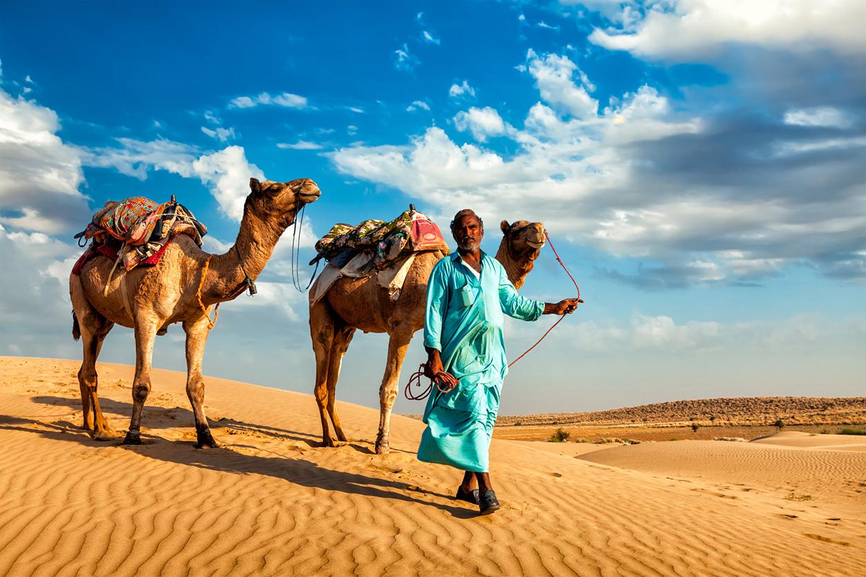Indiano com camelo no deserto de Thar